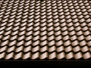 interlocking brown pantile roof tiles form waves across the roof