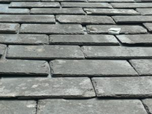 close up of an old slate roof showing signs of wear and tear