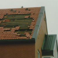 A large section of roof tiles have been blown off this roof